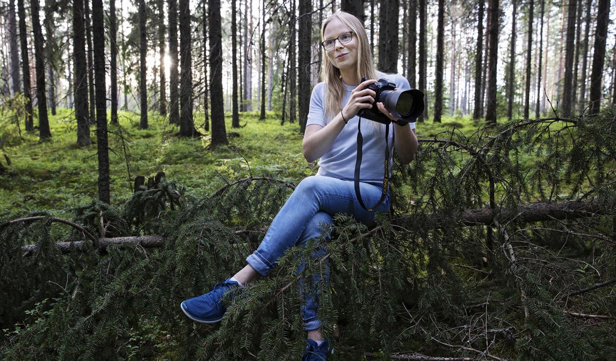 Lina Enlund istuu metsässä kamera kädessä.