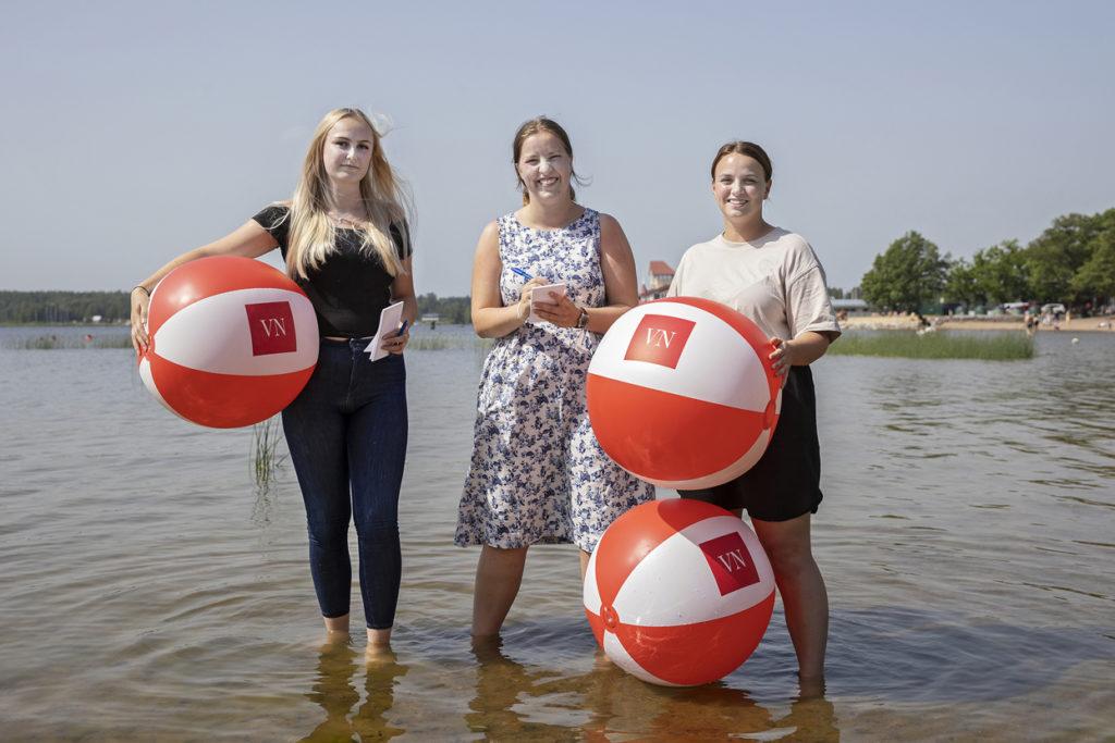 Kolme kesätoimittajaa seisoo vedessä rantapallojen kanssa.