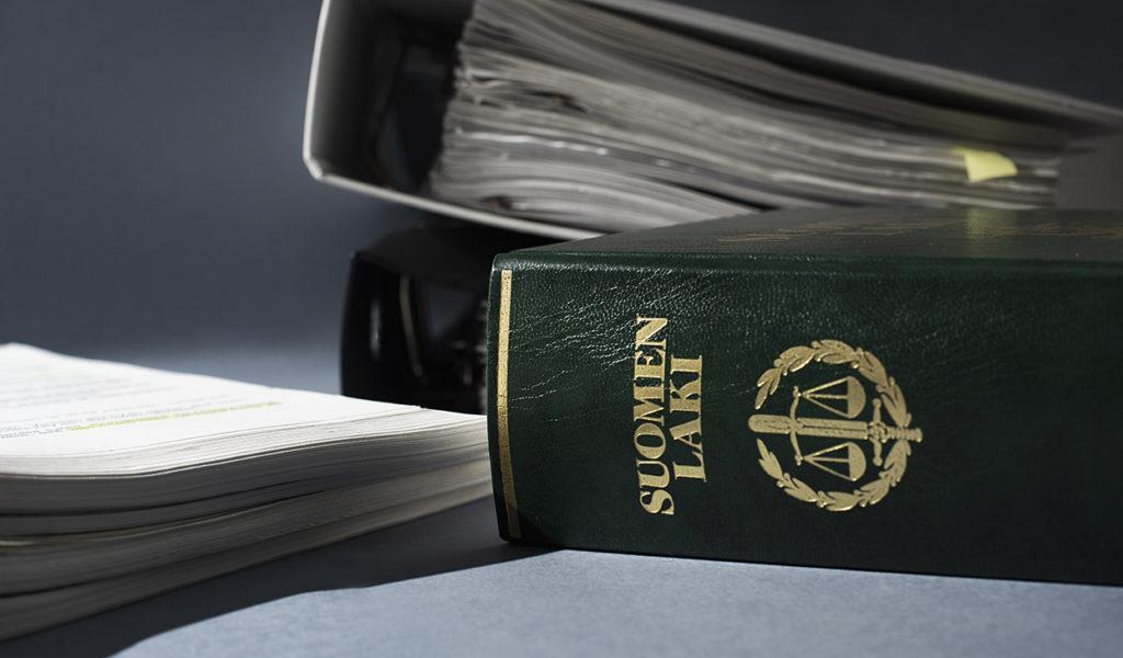 Asiakirjoja pinossa, mappeja taustalla, lakikirja kuvan etualalla.