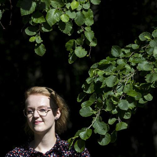 Roosa Sarajärven kasvot, kirkkaassa valossa, lehtiseinän edessä